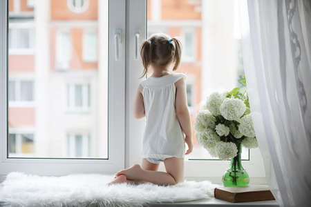 Photo for A little girl is sitting on the windowsill. A bouquet of flowers in a vase by the window and a girl sniffing flowers. A little princess in a white dress with a bouquet of white - Royalty Free Image