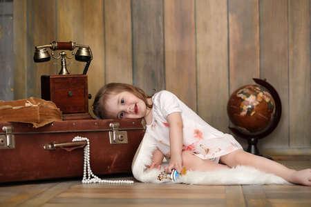 Foto de A child in a retro interior and an old phone sits on the floor. - Imagen libre de derechos