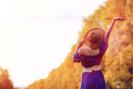 Young beautiful girl in dresses on nature. A girl in a hat walks