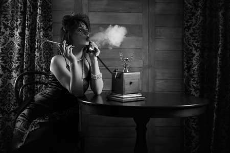 Photo pour Beautiful 1930s girl smokes monochrome - image libre de droit
