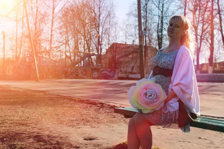 Photo for Pregnant girl on a walk in the park. Girl with a belly in the ci - Royalty Free Image