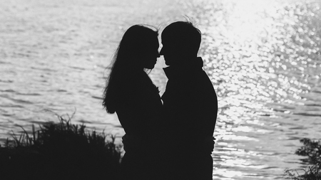 Photo for couple in love hugging by the water, the silhouette - Royalty Free Image