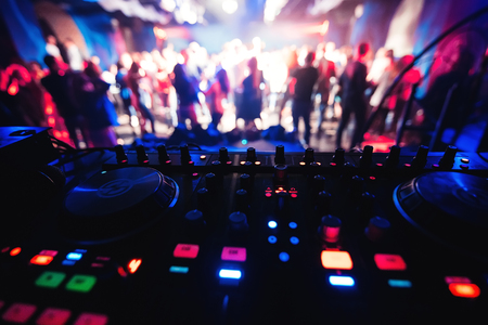 Photo for mixer and DJ booth in the nightclub at party c of multi-colored dancers on the dance floor blurred people - Royalty Free Image
