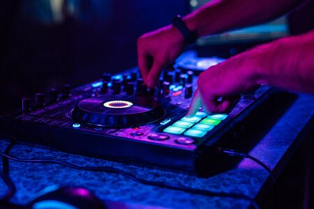 Photo for hands of a DJ playing music on a mixer at a concert - Royalty Free Image