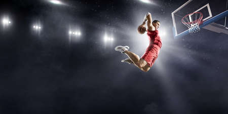 Photo for Baketball player making a slam dunk on a professional basketball arena. He wears unbranded clothing. - Royalty Free Image