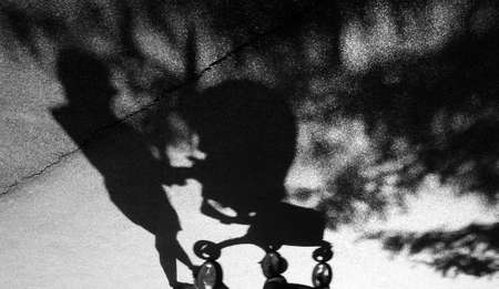 Photo pour Blurry shadow of a woman with postpartum depression pushing a baby trolley on the cracked asphalt suburban park road in black and white - image libre de droit