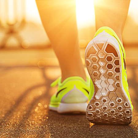 Foto de Runner woman feet running on road closeup on shoe. Female fitness model sunrise jog workout. Sports healthy lifestyle concept. - Imagen libre de derechos