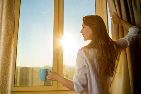Photo for Woman in the morning. Attractive sexy woman with neat body is holding a cup with hot tea or coffee and looking at the sunrise standing near the window in her home and having a perfect cozy morning. - Royalty Free Image