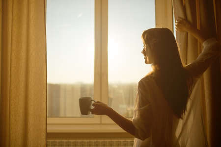 Foto de Woman in the morning. Attractive sexy woman with neat body is holding a cup with hot tea or coffee and looking at the sunrise standing near the window in her home and having a perfect cozy morning. - Imagen libre de derechos