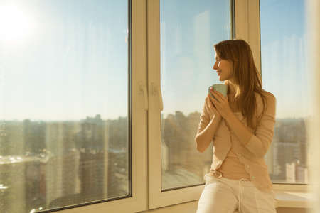 Photo pour Woman in the morning. Attractive tender young woman is holding a cup with hot tea or coffee and looking at the sunrise sitting near the window in her home and having a perfect cozy morning. - image libre de droit