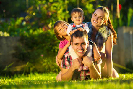 Foto de Happy young family having fun outdoors in summer. Mother, father and their cute little daughters are playing in the sunny garden. Happy parenthood and childhood concept. Focus on the father. - Imagen libre de derechos