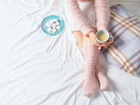 Photo pour Woman relaxing at cozy home atmosphere on the bed. Young woman with cup of coffee or cocoa in hands and cookies enjoying comfort. Soft light and comfy lifestyle concept. - image libre de droit