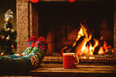 Photo for Feet in woollen socks by the Christmas fireplace. Woman relaxes by warm fire with a cup of hot drink and warming up her feet in woollen socks. Close up on feet. Winter and Christmas holidays concept. - Royalty Free Image