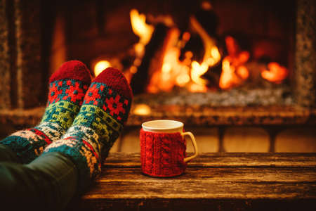 Photo pour Feet in woollen socks by the Christmas fireplace. Woman relaxes by warm fire with a cup of hot drink and warming up her feet in woollen socks. Close up on feet. Winter and Christmas holidays concept. - image libre de droit