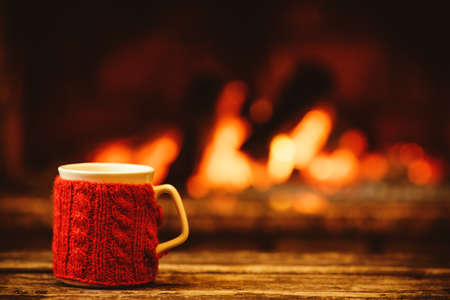 Photo for Cup of hot drink in front of warm fireplace. Holiday Christmas concept. Mug in red knitted mitten standing near fireside. Cozy relaxed magical atmosphere in a chalet. - Royalty Free Image