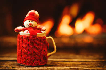 Photo pour Cup of hot drink in front of warm fireplace. Holiday Christmas concept. Mug in red knitted mitten, decorated with snowman toy, standing near fireside. Cozy relaxed magical atmosphere in a chalet. - image libre de droit