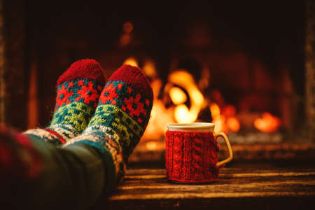 Foto de Feet in woollen socks by the Christmas fireplace. Woman relaxes by warm fire with a cup of hot drink and warming up her feet in woollen socks. Close up on feet. Winter and Christmas holidays concept. - Imagen libre de derechos