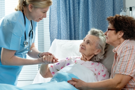 Doctor talking to elderly patient lying in bed in hospital