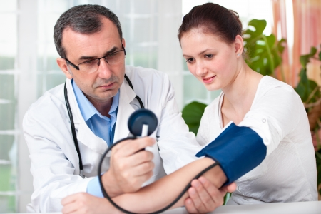 Male doctor checking young woman blood pressure