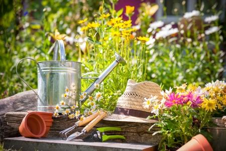 Foto de Gardening tools and a straw hat on the grass in the garden - Imagen libre de derechos