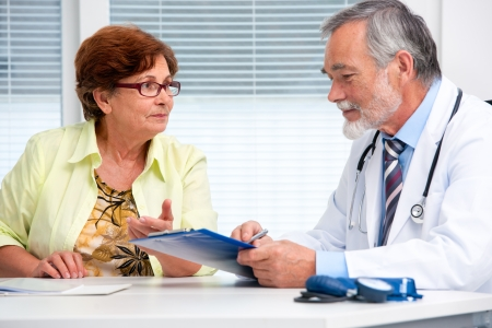 Photo pour Doctor talking to his female senior patient at the office - image libre de droit