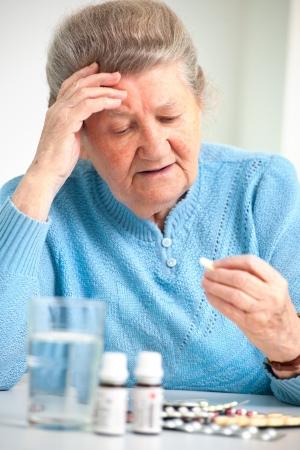Photo pour close-up portrait of an older woman taking a medicine - image libre de droit