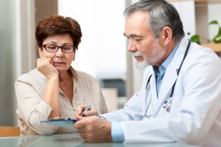 Foto de Doctor talking to his female senior patient at the office - Imagen libre de derechos