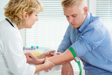 Photo pour Nurse taking blood sample from patient at the doctors office - image libre de droit