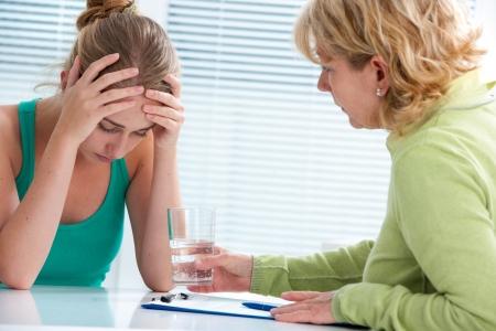 Foto de treenage girl suffering with depression in a conversation with a therapist - Imagen libre de derechos