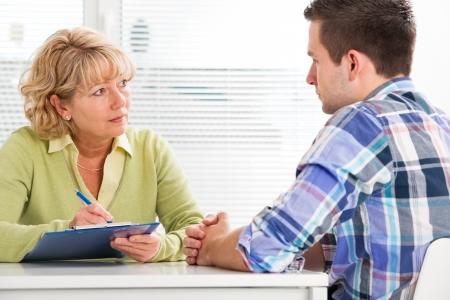 Foto de Doctor talking to her male patient at office - Imagen libre de derechos