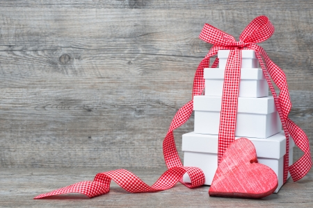 Photo for Stack of gift boxes with ribbon and bow  on old wooden background - Royalty Free Image