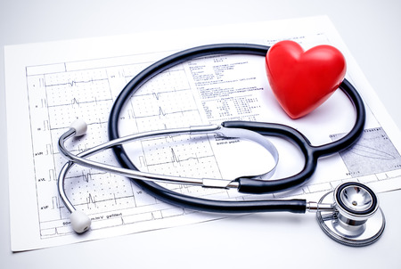Photo for Stethoscope with a red heart on the top of the ECG chart - Royalty Free Image