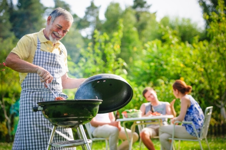 Photo for Family having a barbecue party in their garden in summer - Royalty Free Image