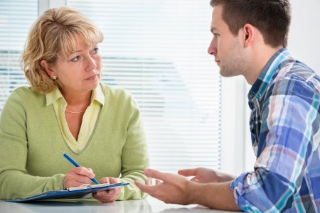 Photo pour Teenager having a  therapy session while therapist is taking notes - image libre de droit