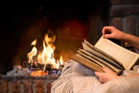 Photo pour hands of woman reading book by fireplace - image libre de droit
