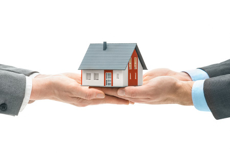 Photo pour Hands giving house model to other hands. Concept of real estate and deal - image libre de droit