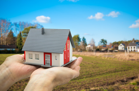 Photo pour Hands holding a house model against building ground  - image libre de droit