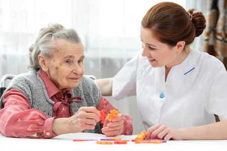 Foto de Nurse helps the senior woman jigsaw puzzle to solve in a nursing home - Imagen libre de derechos