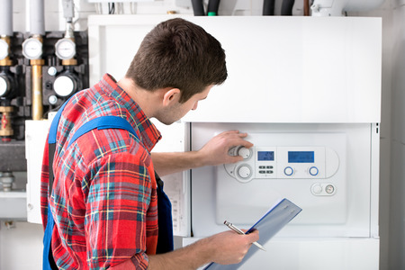 Photo pour Technician servicing the gas boiler for hot water and heating - image libre de droit