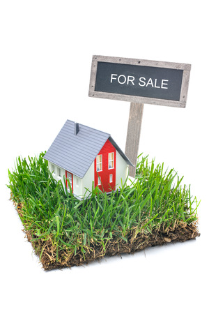 Photo pour For sale sign and house in green grass. Isolated on white background - image libre de droit