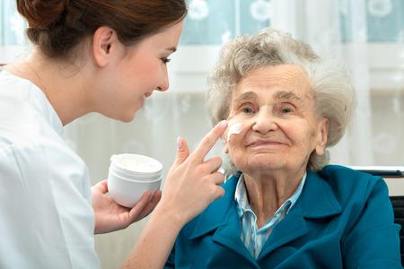Foto de Nurse assists an elderly woman with skin care and hygiene measures at home - Imagen libre de derechos
