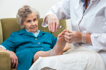 Photo pour Nurse assists an elderly woman with chiropody and body care at home - image libre de droit