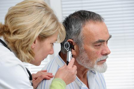 Foto de ENT physician looking into patient's ear with an instrument - Imagen libre de derechos