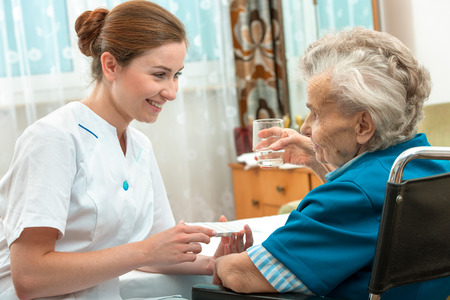 Photo for female nurse giving senior woman medical pills - Royalty Free Image