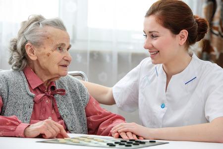 Foto de Senior woman playing checkers with a nurse in a retirement home - Imagen libre de derechos