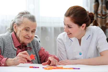 Foto de Elder care nurse playing jigsaw puzzle with senior woman in nursing home - Imagen libre de derechos