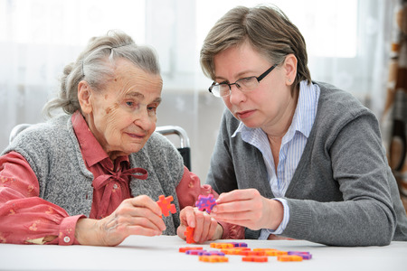 Photo for Elder care nurse playing jigsaw puzzle with senior woman in nursing home - Royalty Free Image