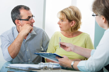 Photo pour Mature couple getting financial advice from consultant at home - image libre de droit