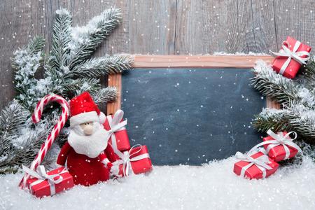 Foto de Vintage Christmas decoration with Santa Claus und chalkboard for message - Imagen libre de derechos