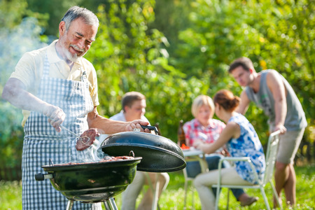 Photo pour Family having a barbecue party in their garden in summer - image libre de droit
